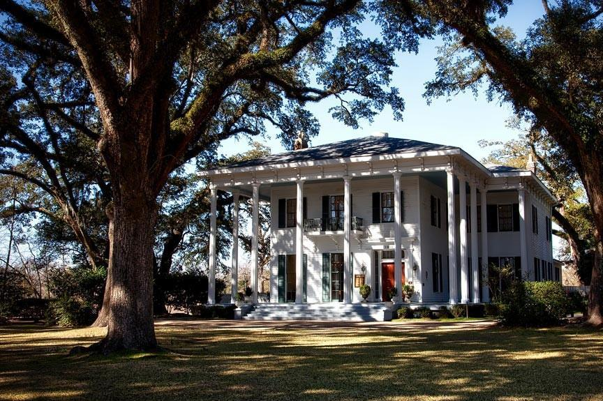 PLANTATION STYLE WHITE MANSION SURROUNDED BY WEEPING WILLOW TREES